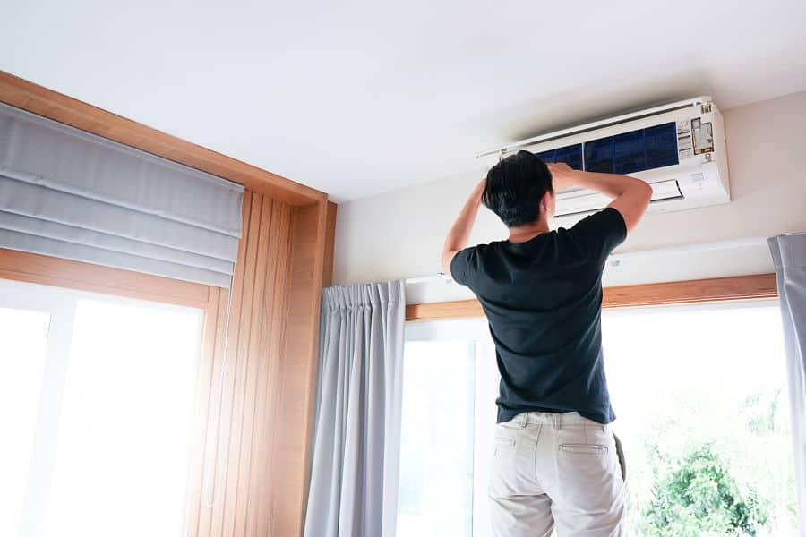 Technician man repairing ,cleaning and maintenance Air conditioner on the wall in bedroom.On site home service,Business ,Industrial concept.